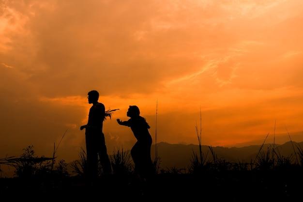 Heureux couple enfants jouant sur prairie au coucher du soleil, silhouette