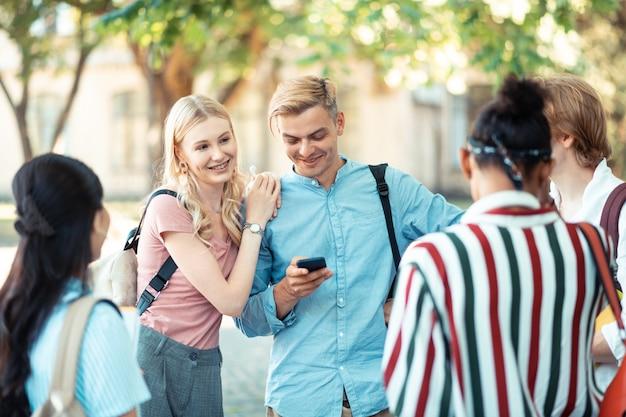 Heureux couple d'étudiants debout devant leurs camarades de groupe à l'extérieur de l'université