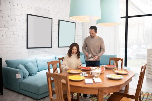 Heureux couple examinant les meubles dans une pièce lumineuse