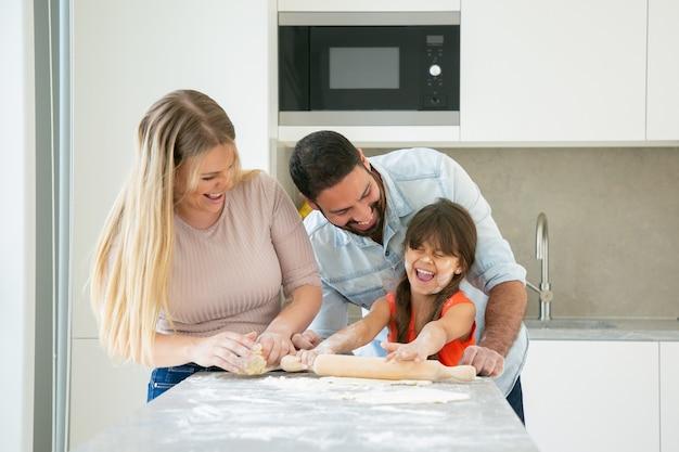 Heureux couple excité et fille avec de la poudre de fleur sur le visage en riant pendant la cuisson ensemble.