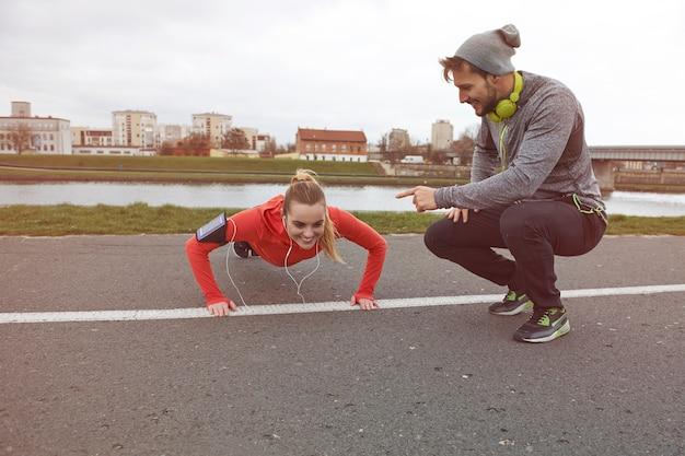 Heureux couple exerçant à l'extérieur. continue! tu peux le faire!