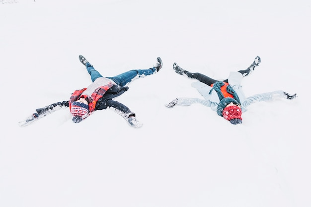 Heureux couple faisant des anges dans la neige