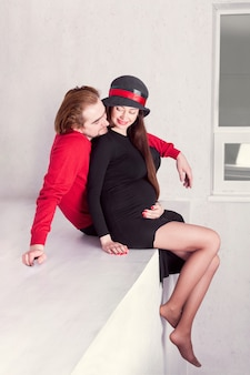 Heureux couple de fille enceinte assise avec son mari dans une pièce blanche et se tenant le ventre
