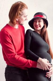 Heureux couple de fille enceinte qui se tient avec son mari et se tient le ventre