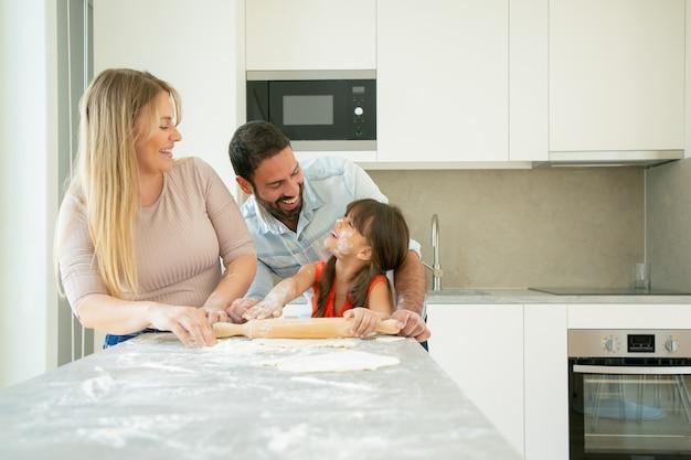 Heureux couple et fille avec une fleur sur le visage appréciant la cuisson ensemble.