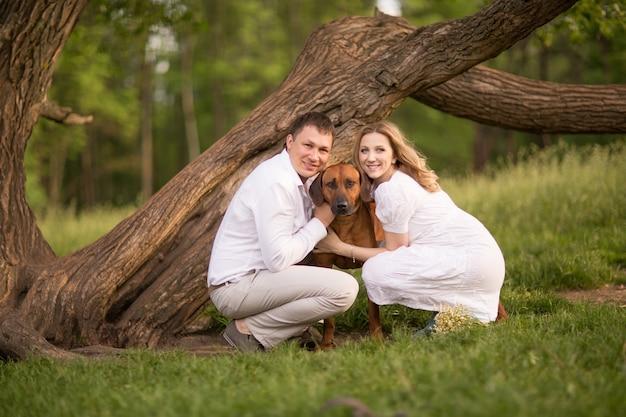 Heureux couple futurs parents sur la promenade avec le chien dans le parc