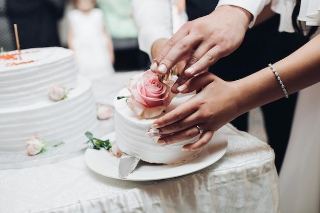 Heureux couple gardant un couteau et un délicieux gâteau de mariage
