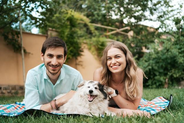 Heureux couple de gars jouant avec leur chien dans la cour sur l'herbe. joyeux vieux chien