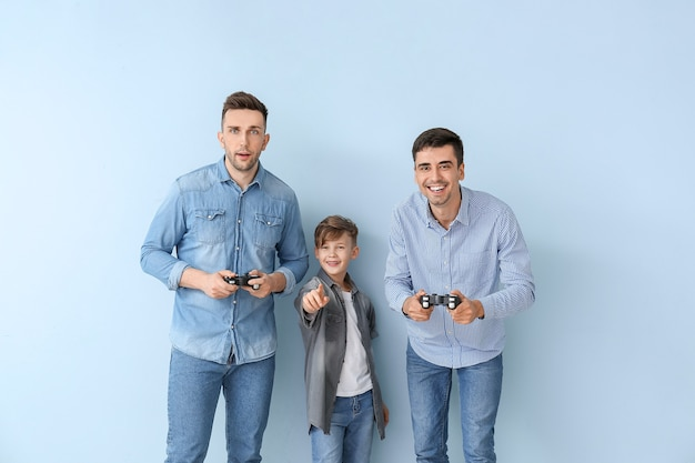 Heureux couple gay avec enfant adopté jouant au jeu vidéo sur fond de couleur
