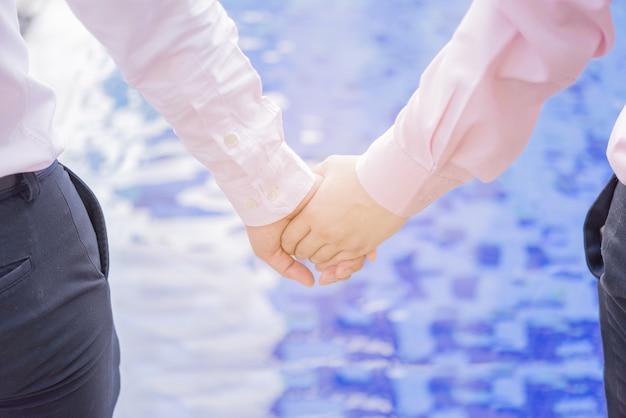 Heureux couple gay tenant par la main.