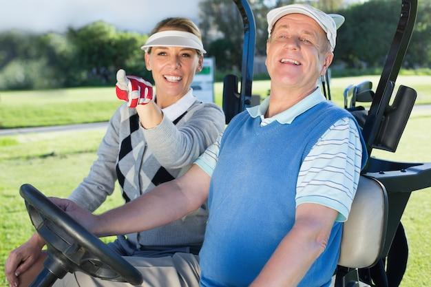 Heureux couple de golf assis dans une voiturette de golf
