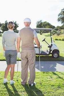 Heureux couple de golf donnant sur le parcours