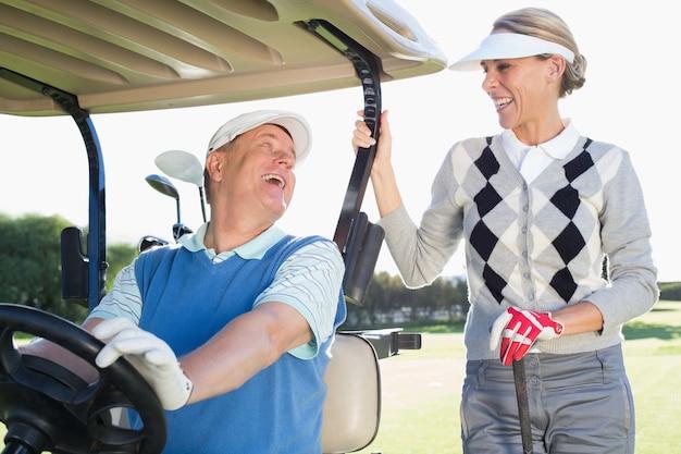 Heureux couple golfeur partant pour la journée en buggy