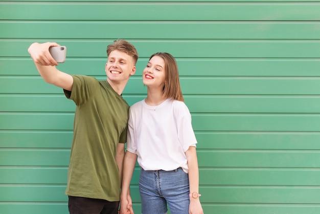 Heureux couple jeune homme et fille prendre selfie sur turquoise, regardant la caméra et souriant