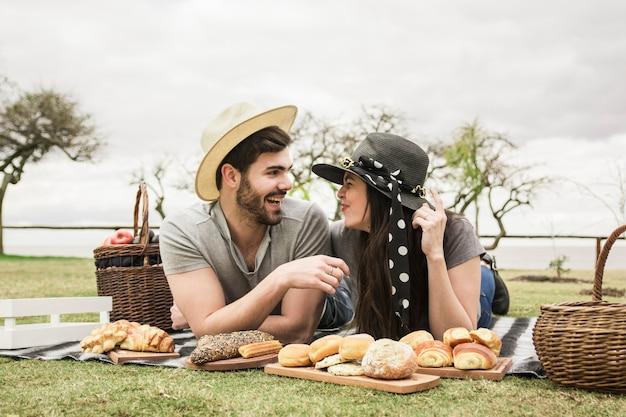 Heureux couple de jeunes amoureux se trouvant sur une couverture avec des pains cuits au four à pique-nique