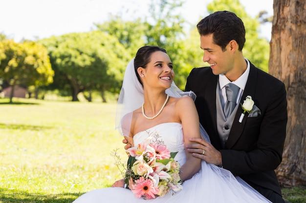 Heureux couple de jeunes mariés assis dans le parc