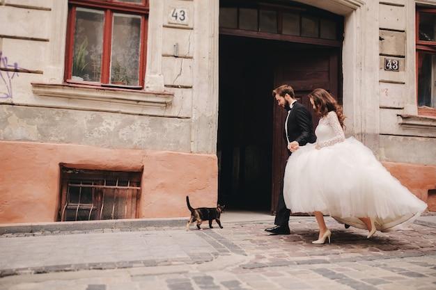 Heureux couple de jeunes mariés étreignant et s'embrassant dans la vieille rue de la ville européenne, magnifique mariée en robe de mariée blanche avec beau marié. jour de mariage.