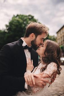 Heureux couple de jeunes mariés étreindre et s'embrasser dans la vieille rue de la ville européenne