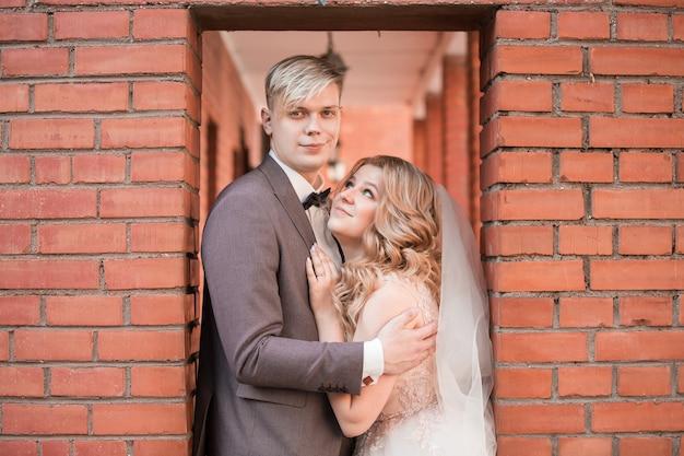 Heureux couple de jeunes mariés s'embrassant en marchant. vacances et événements
