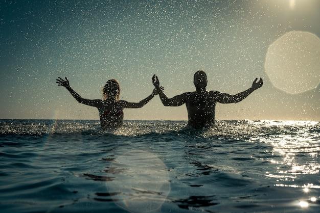Heureux couple jouant dans la mer homme et femme s'amusant en vacances d'été concept de mode de vie sain et actif