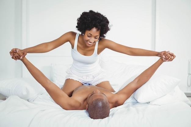 Heureux couple jouant sur le lit à la maison