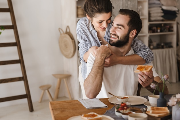 Heureux couple joyeux prenant un délicieux petit-déjeuner à la cuisine