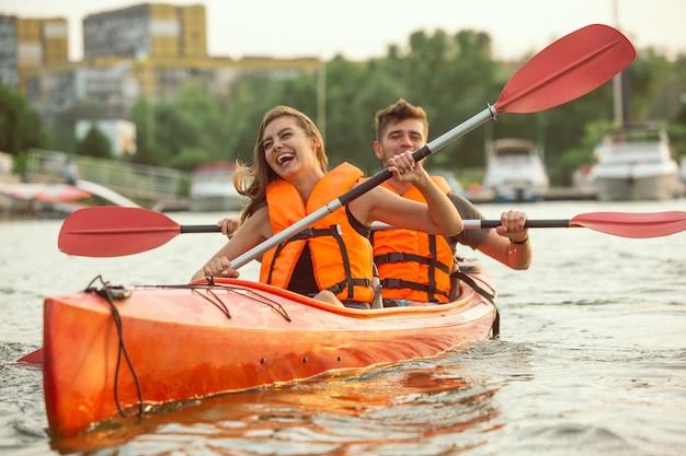 Heureux couple kayak sur la rivière avec coucher de soleil en arrière-plan