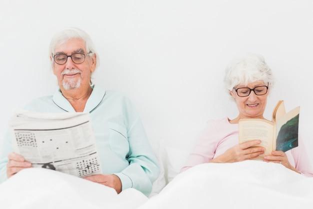 Heureux couple lisant au lit