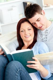 Heureux couple lisant un livre dans le salon allongé sur le canapé