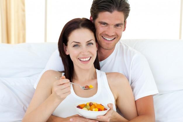 Heureux couple mangeant des fruits allongés sur leur lit