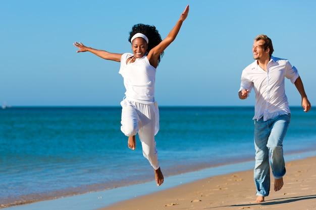 Heureux couple marchant et courant sur la plage