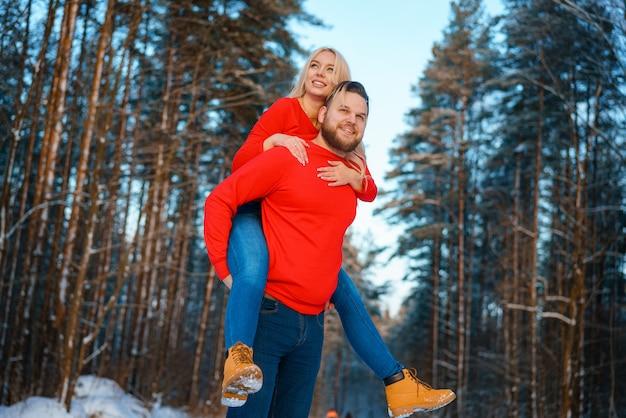 Heureux couple marchant dans la forêt enneigée