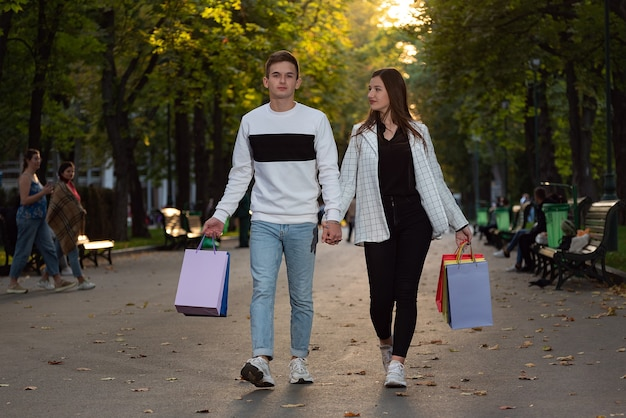 Heureux couple marchant dans le parc avec des sacs colorés avec des souvenirs. le jeune homme et la femme marchent ensemble.
