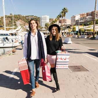 Heureux couple marchant dans la rue avec des sacs