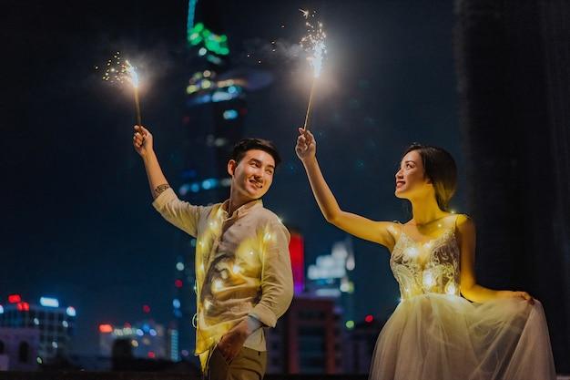 Heureux couple marchant avec feux d'artifice sparkler dans la main dans l'obscurité