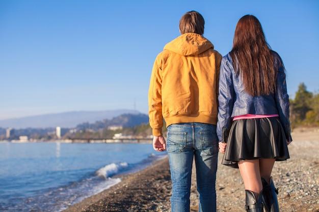 Heureux couple marchant sur la plage un jour d'hiver ensoleillé