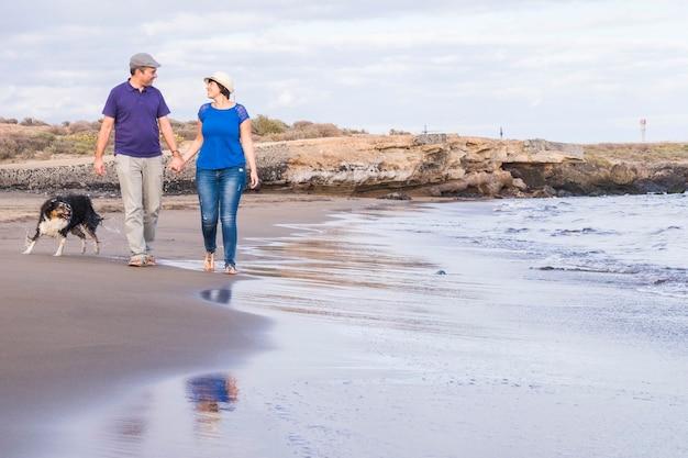 Heureux couple marche sur le rivage sur la plage avec les vagues de l'océan et le border collie.