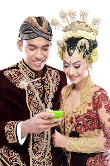 Heureux couple de mariage java traditionnel avec téléphone portable