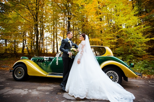 Heureux couple de mariage de luxe s'embrassant et embrassant près de rétro avec voiture bouquet en automne