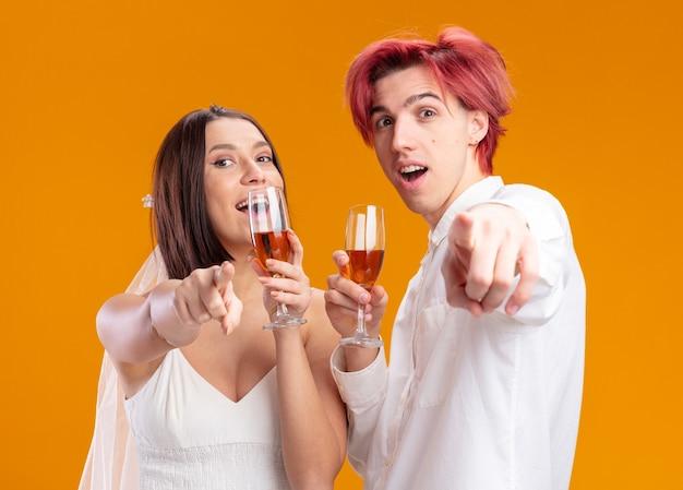Heureux couple de mariage marié et mariée en robe de mariée souriant joyeusement posant ensemble tenant des verres de champagne pointant avec l'index à l'avant