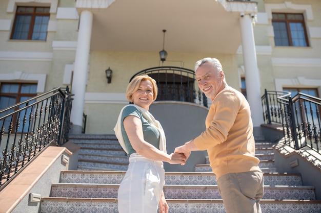 Heureux couple marié d'âge moyen debout sur les marches