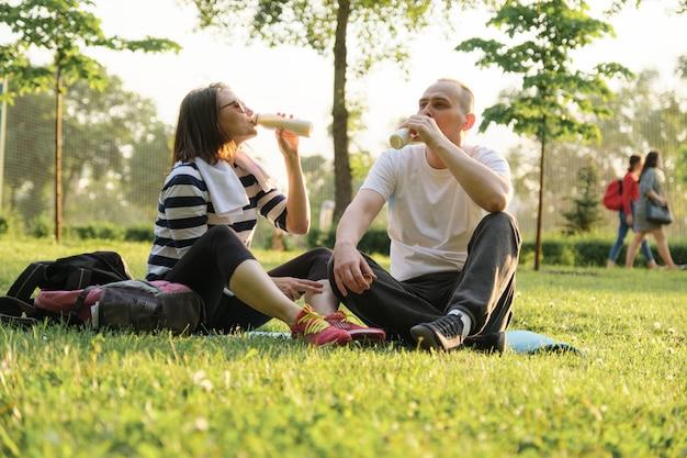 Heureux couple mature assis dans le parc sur un tapis de fitness