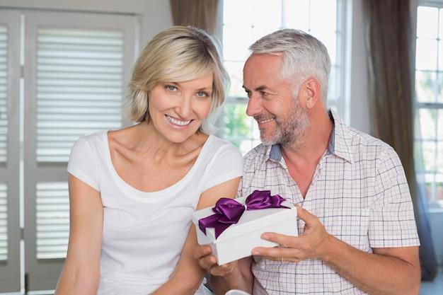 Heureux couple mature avec une boîte-cadeau à la maison