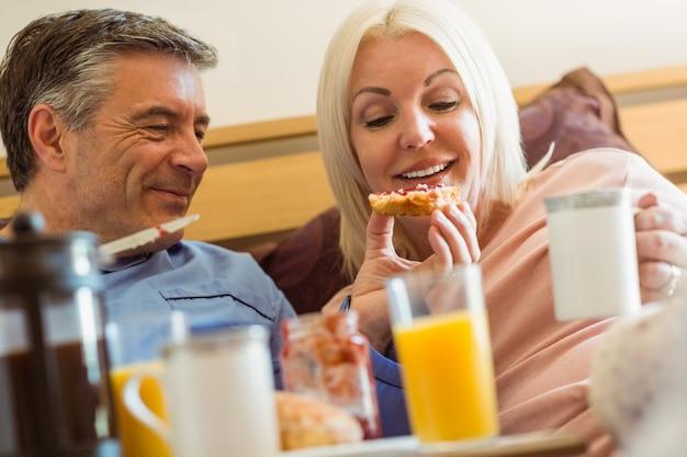 Heureux couple mature prenant son petit déjeuner au lit