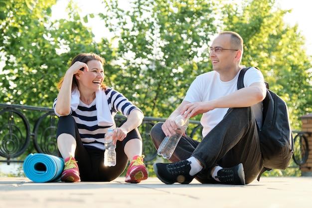 Heureux couple mature souriant assis dans le parc, parler au repos après avoir fait du sport