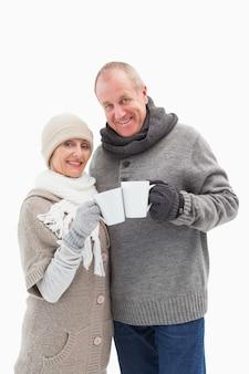 Heureux couple mature en vêtements d'hiver tenant des tasses
