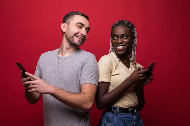 Heureux couple métis, envoi de messages texte du téléphone côte à côte sur fond rouge