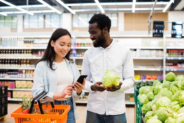 Heureux couple multiethnique choisissant des marchandises en supermarché