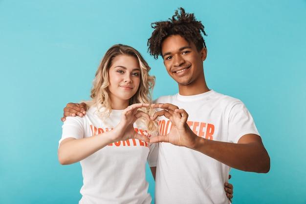 Heureux couple multiethnique confiant portant des volontaires t-shirt isolé sur mur bleu, geste de coeur