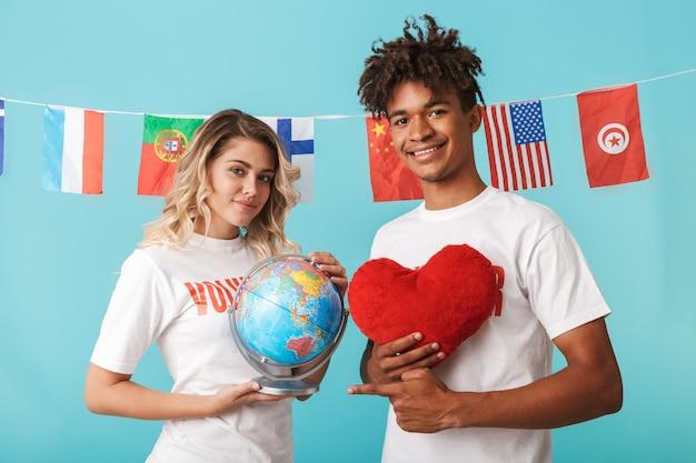 Heureux couple multiethnique confiant portant des volontaires t-shirt isolé sur un mur bleu, tenant un globe terrestre et un coeur rouge